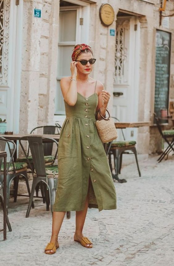 a green midi dress with spaghetti straps, buttons, brown slippers, a straw bag and a colorful bandana