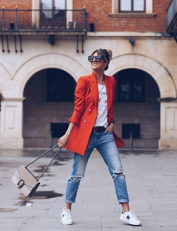 a white printed tee, blue ripped jeans, white sneakers, an oversized orange blazer and a neutral bag