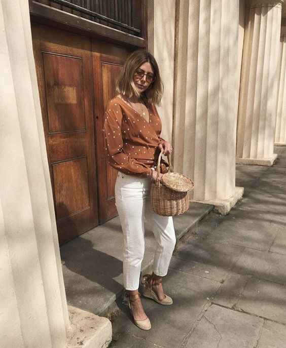 white cropped jeans, a rust-colored polka dot wrap shirt, espadrilles and a basket bag