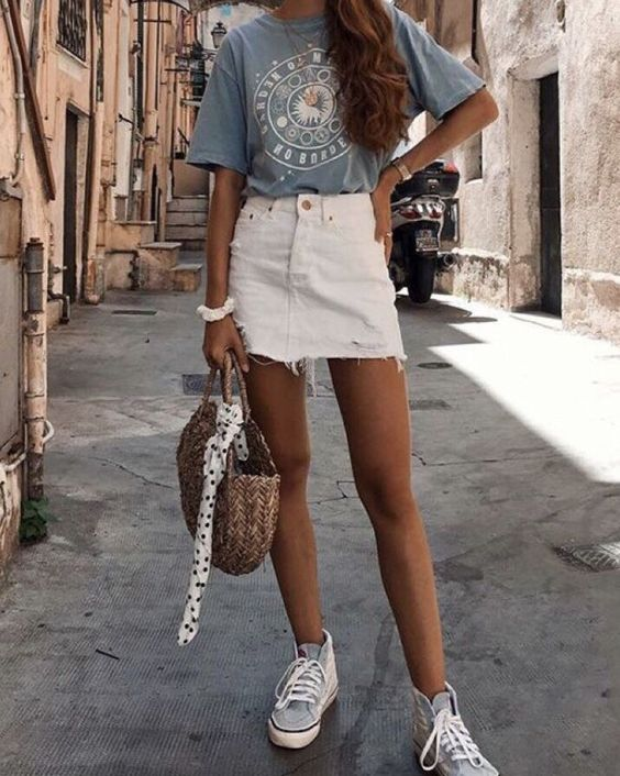 a blue printed tee, a white denim mini skirt, blue sneakers and a straw bag