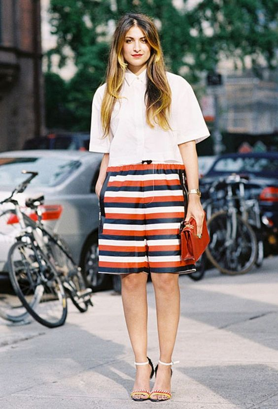 a white oversized button up, striped long shorts, a red bag and bright shoes to create a summer office look