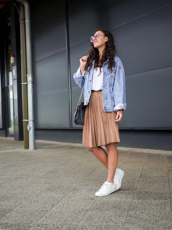 a white tee, a beige pleated knee skirt, white sneakers and a blue oversized denim jacket