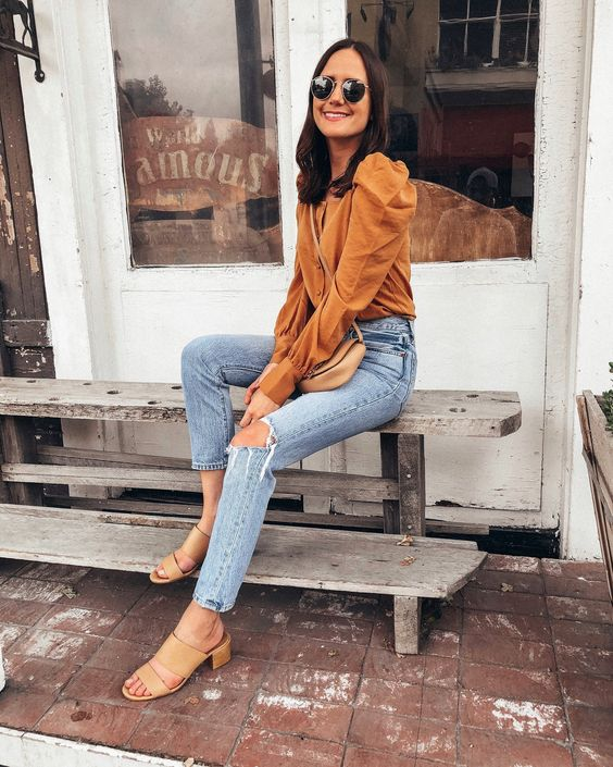 blue ripped jeans, nude heeled sandals and a marigold top with puff sleeves