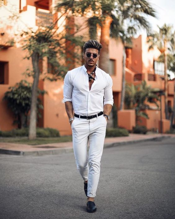 a dashing outfit with neutral pants and a white shirt, black loafers and a neck tie