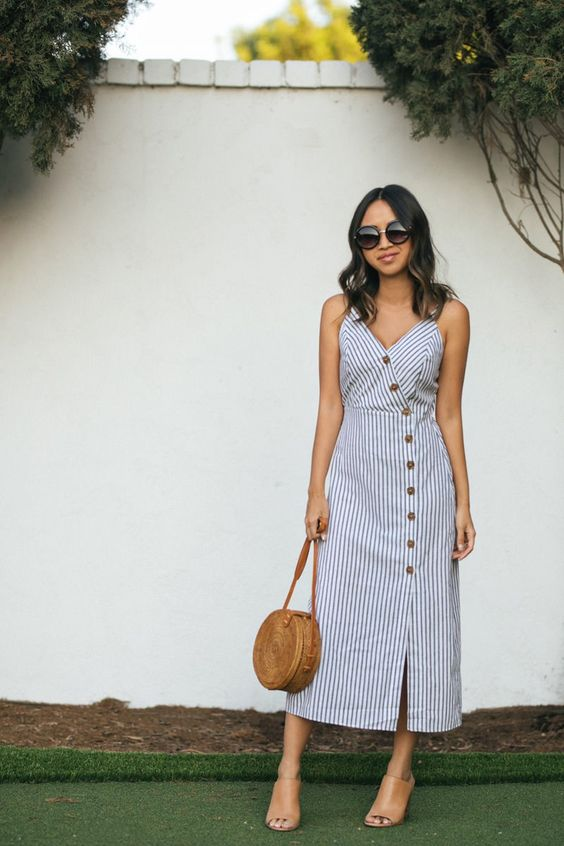 a striped blue and white midi dress with buttons, amber mules and a brown round bag