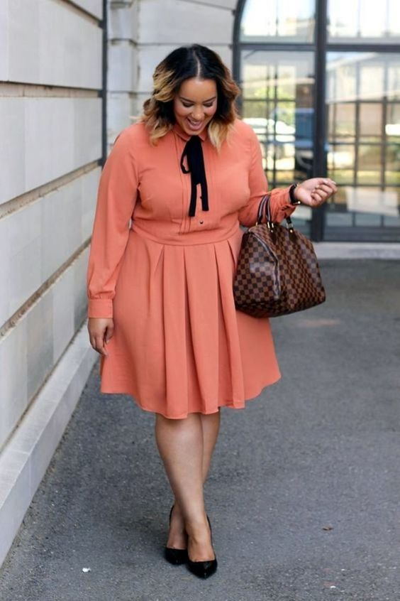 a coral knee dress with a black bow, black shoes and a plaid bag for a bright fall office look