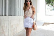 11 a retro-inspired look with a white denim mini on buttons, a neutral top with lacing, nude heels and a nude bag