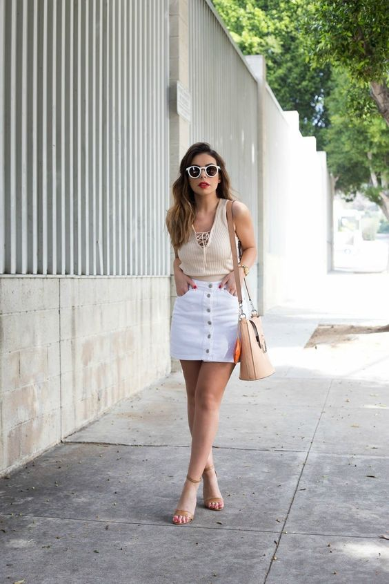 a retro-inspired look with a white denim mini on buttons, a neutral top with lacing, nude heels and a nude bag