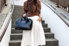 12 a brown top with long sleeves, a white pleated midi, nude shoes and a black bag