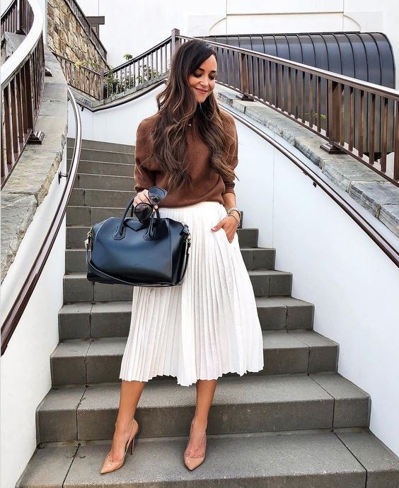 a brown top with long sleeves, a white pleated midi, nude shoes and a black bag
