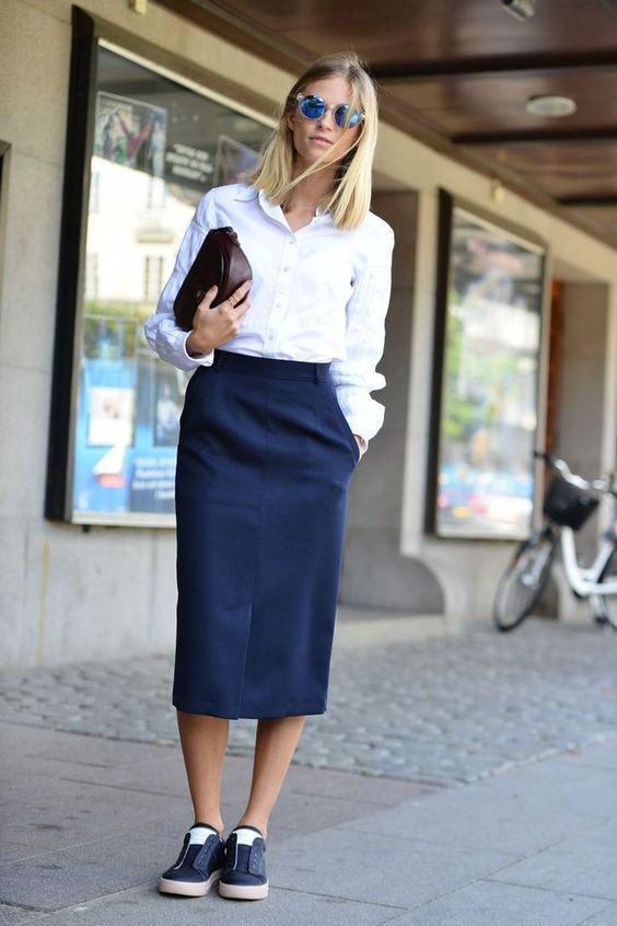 a business casual look with a white shirt, a navy pencil midi and matching sneakers plus a clutch