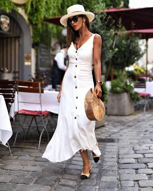 a white A line midi dress with a row of black buttons, two tone shoes and a straw hat for a holiday look