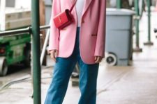 13 a bright trendy outfit with blue jeans, a white top, an oversized pink blazer, a red bag and neutral heels