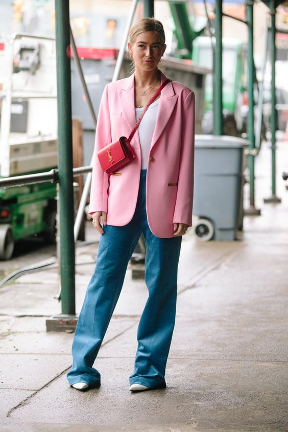 a bright trendy outfit with blue jeans, a white top, an oversized pink blazer, a red bag and neutral heels