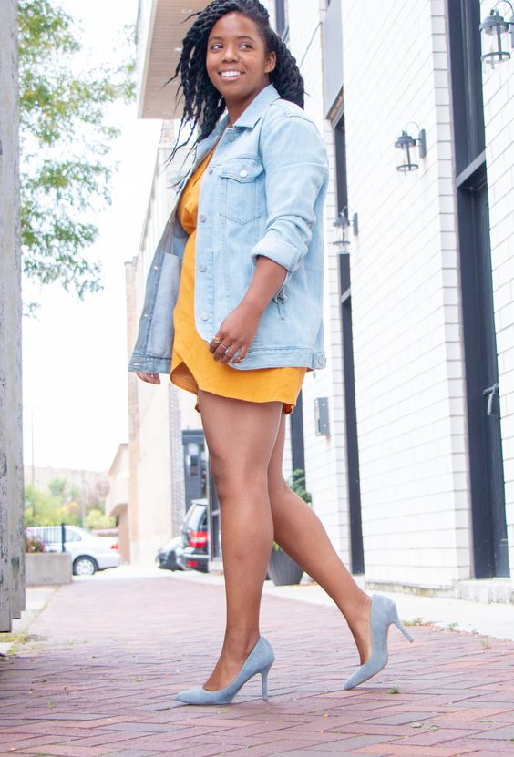 a marigold mini dress, light blue shoes and a bleached oversized denim jacket