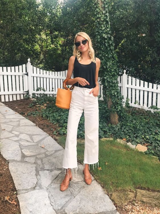a relaxed outfit with straight white jeans with a raw hem, a black top, brown shoes and an amber bag