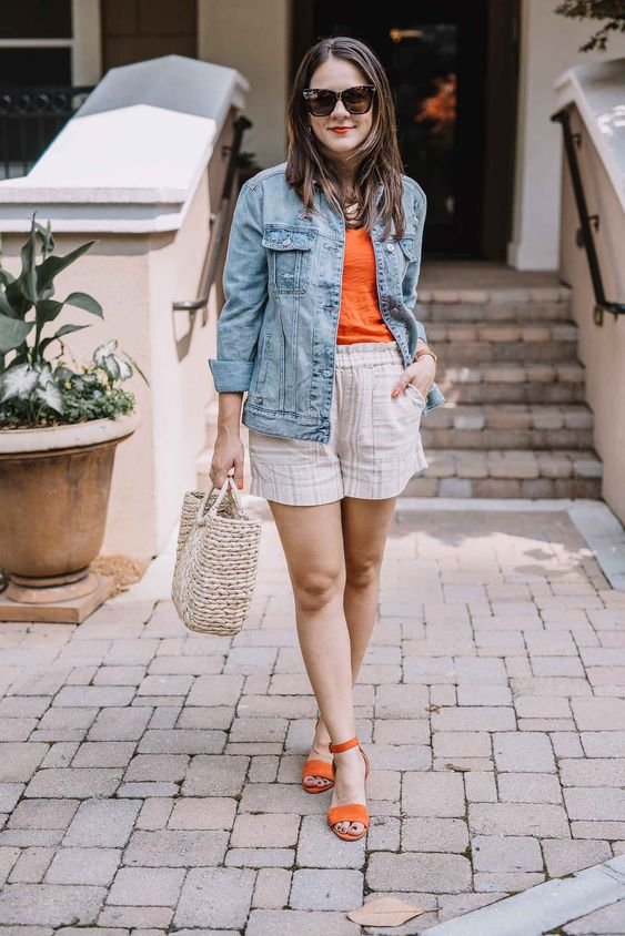 a simple summer look with printed shorts, an orange tee and mathing shoes, a blue denim jacket and a straw bag