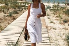 13 a white midi dress with a bodice on thick straps and an A-line skirt with black buttons, espadrilles, a straw bag and hat