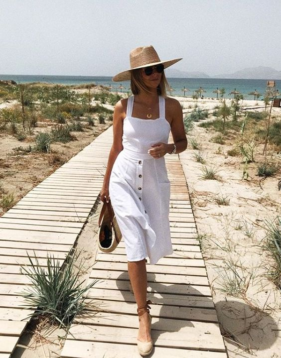 a white midi dress with a bodice on thick straps and an A line skirt with black buttons, espadrilles, a straw bag and hat