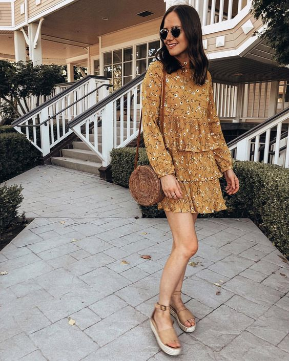 a mustard floral mini dress with long sleeves, a wicker round bag, nude platform shoes