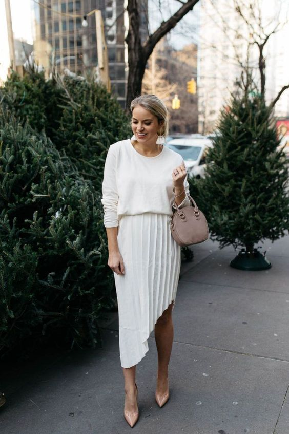a pleated asymmetrical skirt in white, a white top, blush shoes and a small bag for a chic neutral look