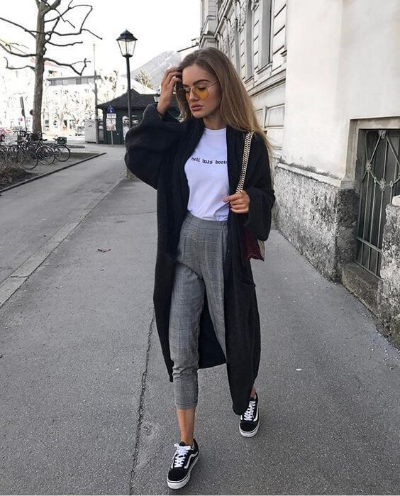 a white printed tee, grey plaid pants, black sneakers and a black long cardigan for comfort