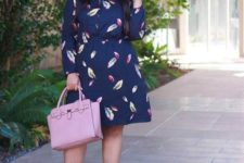 15 a navy A-line knee dress with long sleeves, navy ankle strap shoes and a pink bag for a chic look
