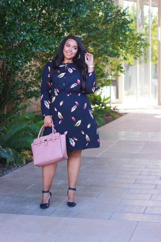 a navy A-line knee dress with long sleeves, navy ankle strap shoes and a pink bag for a chic look