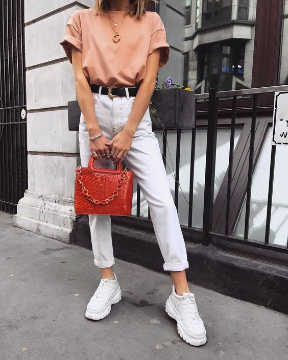 a pink oversized tee, white jeans with a black belt, white sneakers and a red bag