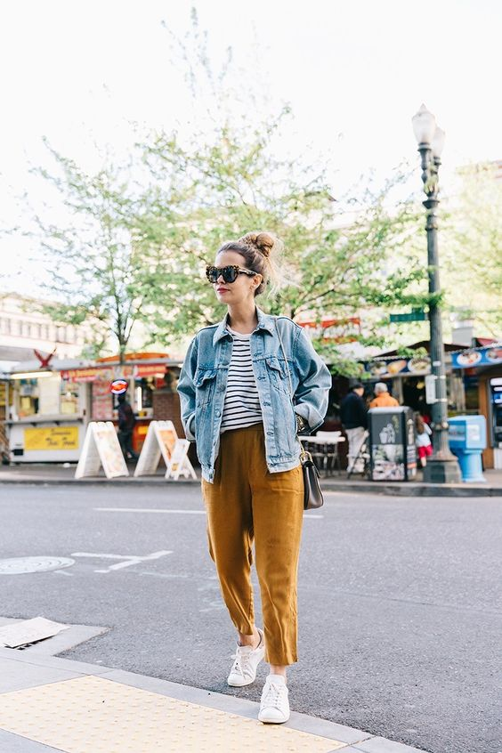 a striped tee, ocher cropped pants, white sneakers and a blue oversized denim jacket