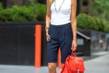 15 a white sleeveless top, navy long shorts, brown heels and a red backpack for a summer look