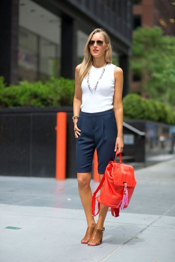 a white sleeveless top, navy long shorts, brown heels and a red backpack for a summer look