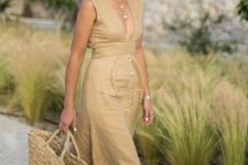 15 an ocher linen midi dress with a plunging neckline, a row of buttons on the skirt, espdarilles, a straw bag and hat
