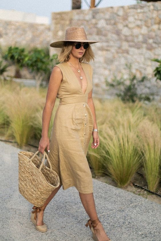 an ocher linen midi dress with a plunging neckline, a row of buttons on the skirt, espdarilles, a straw bag and hat