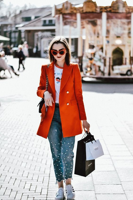 a printed tee, pearly denim, white sneakers, an orange oversized blazer and a black bag