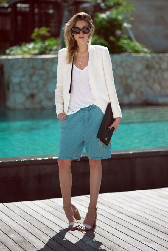 a white tee, a creamy blazer, turquoise denim long shorts, white heels and a black bag