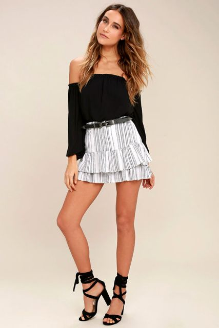 With black off the shoulder top and black lace up high heels
