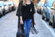 With black top, black leather bag, high heels and distressed cuffed jeans