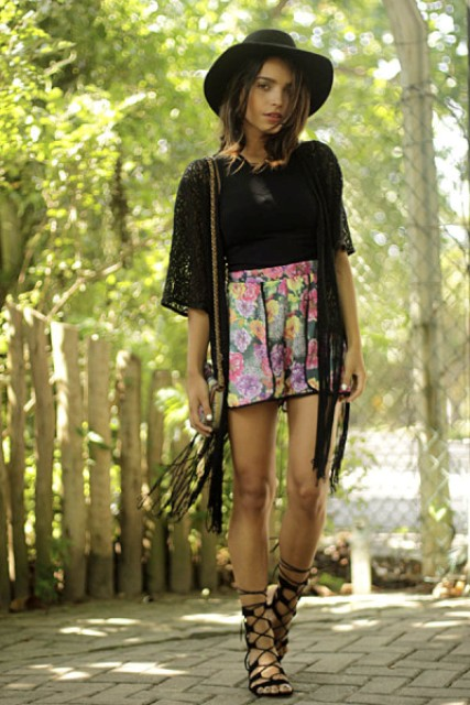 With floral high-waisted shorts, black shirt, hat, chain strap bag and lace up sandals