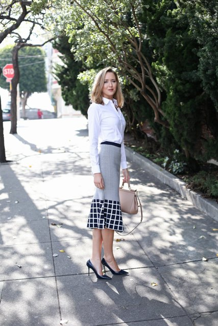 With white button down shirt, beige bag and black pumps