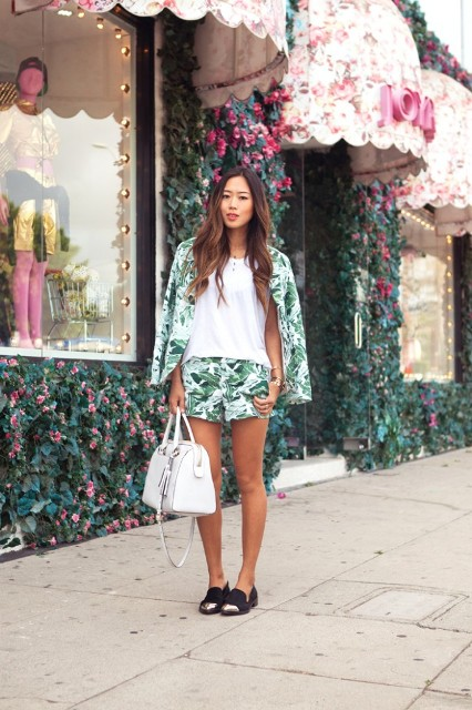 With white loose top, tropical shorts, white bag and black flat shoes