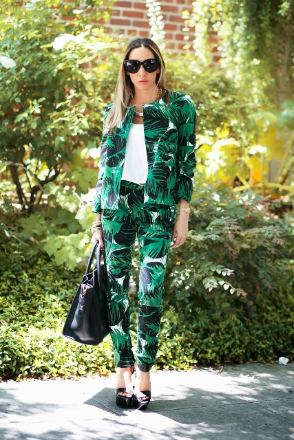 With white top, black tote bag, tropical printed pants and black platform sandals