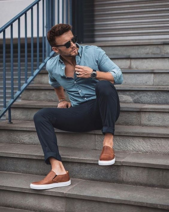a blue chambray shirt, black rolled up pants, brown slipons make up a stylish and comfortable outfit