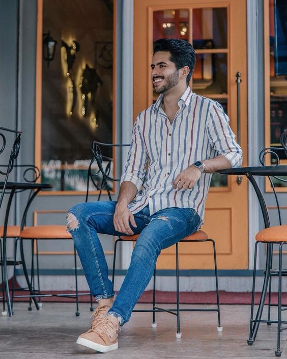 a colorful striped shirt, blue ripped jeans and amber sneakers make up an outfit that feels like summer