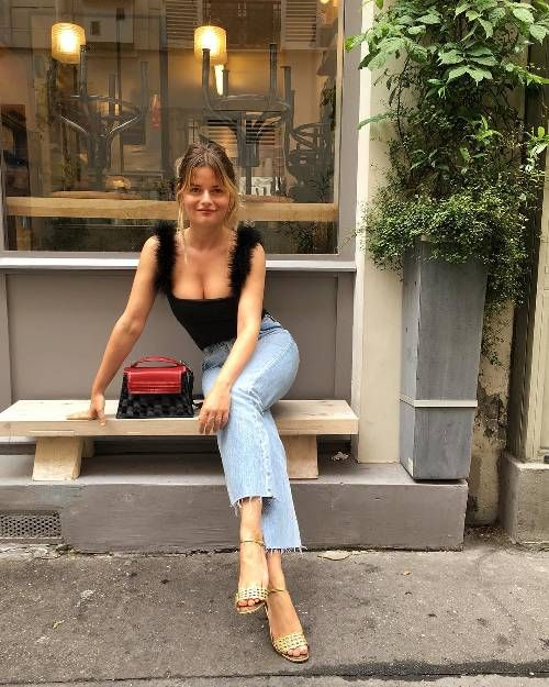 a date look with bleached raw hem jeans, embellished sandals, a black top with fluffs and a red bag