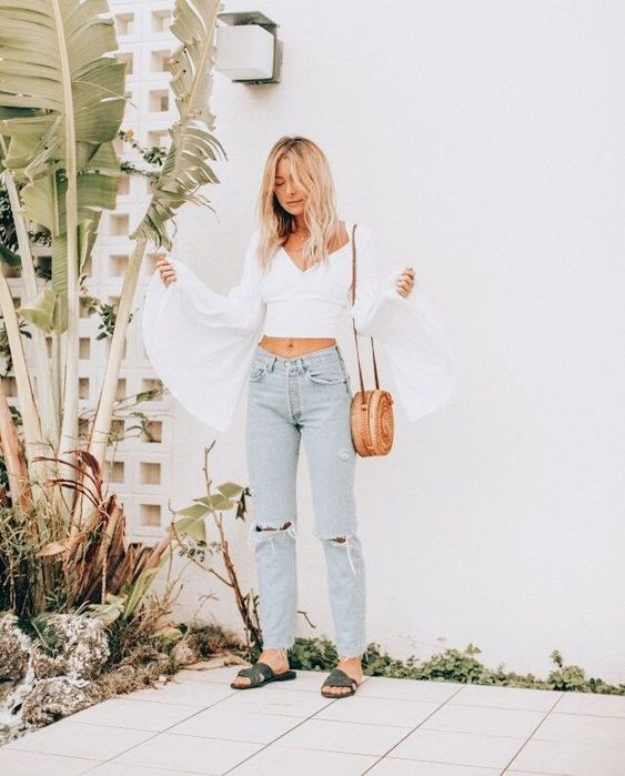 a summer boho look with bleached ripped jeans, grey sandals, a white blouse with bell sleeves and a deep cut