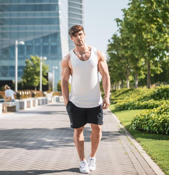 a white tank top, black shorts and white trainers for a stylish monochromatic look in summer