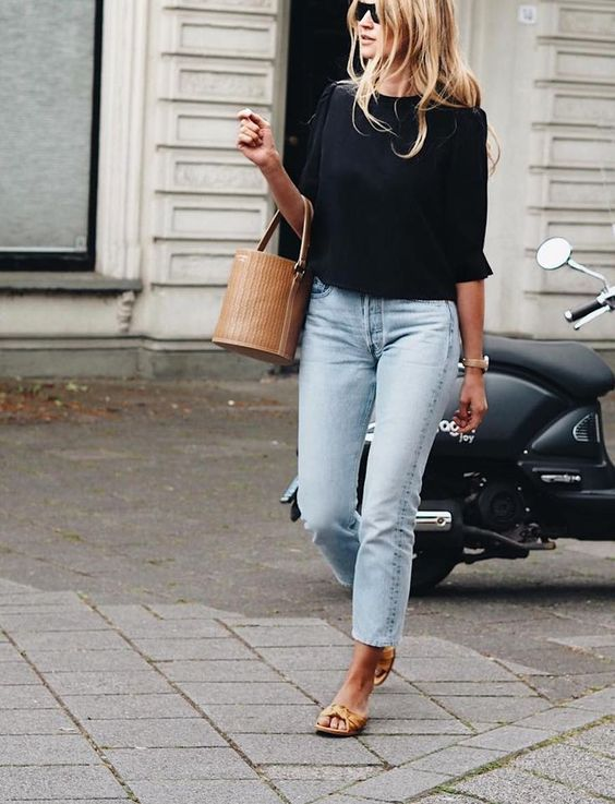 bleached cropped jeans, a black top with short sleeves, a wicker bag and chic brown sandals
