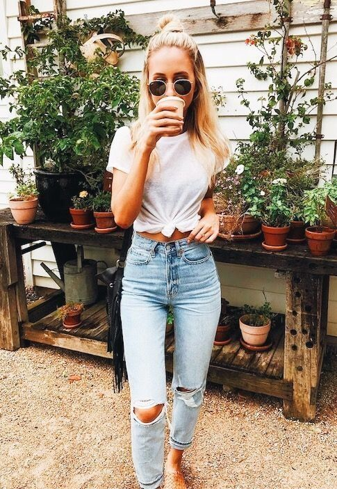 bleached high waisted mom jeans, a tied up t shirt, slippers and a fringe bag
