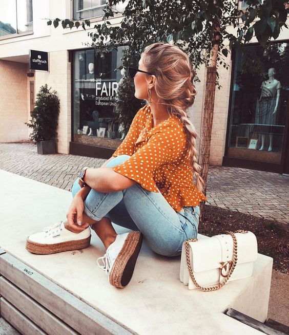 bleached skinnies, a rust colored polka dot shirt, white sneakers and a white bag for a summer to fall look